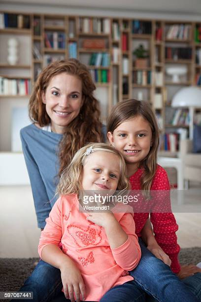 Portrait of two little sisters and her mother in the background sitting on the floor at living room