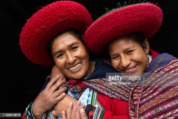 portrait of two local women who are close friends, in colourful, predominantly red, traditional local dress and hats, chinchero, sacred valley, peru (model releases) - ラテンアメリカ ストックフォトと画像