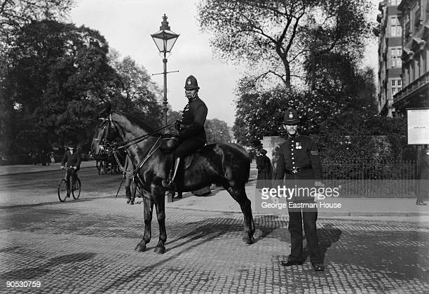 Portrait of two London policemen on a city street one sits atop a horse ca1900s A bicyclist and pedestrian can be seen in the background
