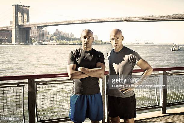 Portrait of two male runners on waterfront, New York City, USA