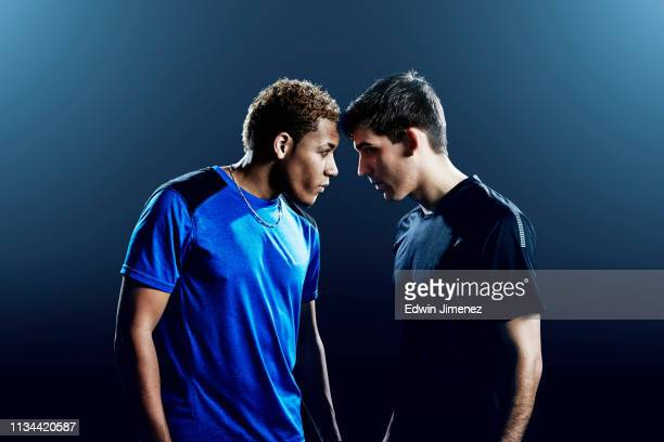 portrait of two male soccer players head to head - rivaliteit stockfoto's en -beelden