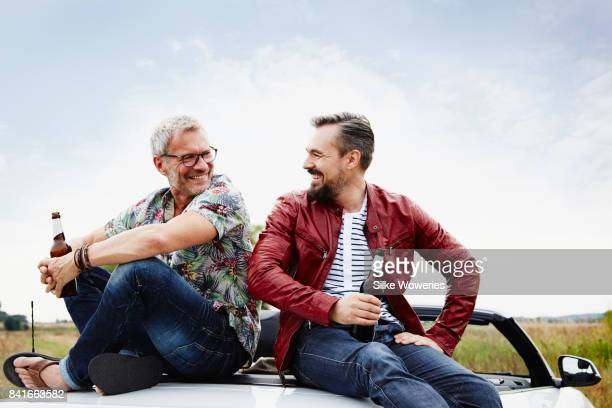portrait of two mature adult men taking a break from driving sitting on the trunk - men friends beer outside stock pictures, royalty-free photos & images