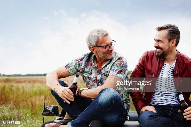portrait of two mature adult men taking a break from driving sitting on the trunk