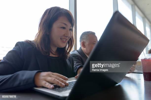 2 つの成熟したアジアのビジネスマンとショッピング モールでレストランの中に楽しみながら働く実業家の肖像画