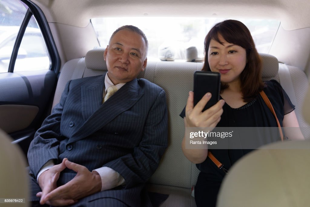 Portrait of two mature Asian businessman and mature Asian woman inside the  car : Stock Photo
