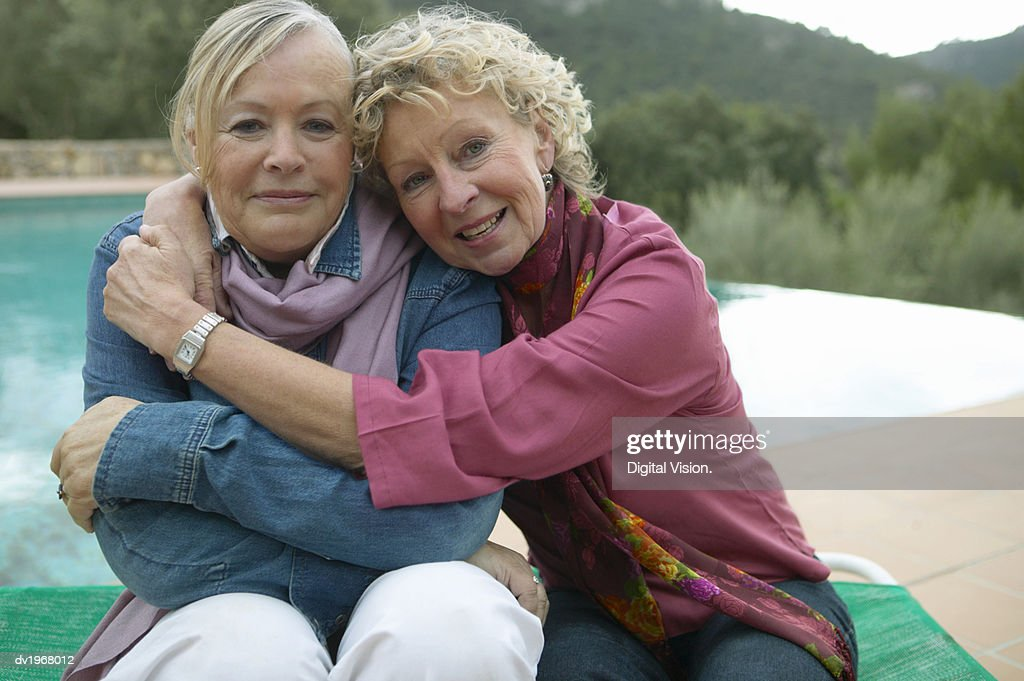 Portrait of Two Mature Friends Sitting Together by a Swimming Pool : Stock Photo