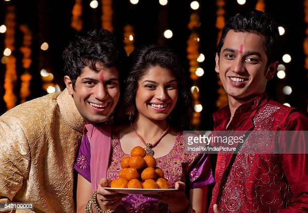 portrait of two men and a woman holding sweets - mithai stock pictures, royalty-free photos & images