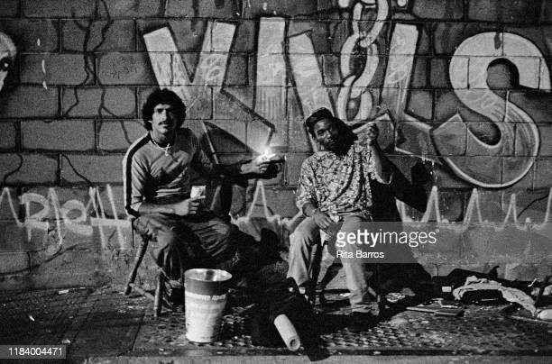 Portrait of two men both with cigarette lighters as they sit on chairs in front of a sidewalk mural 'Crack Kills' New York New York 1990
