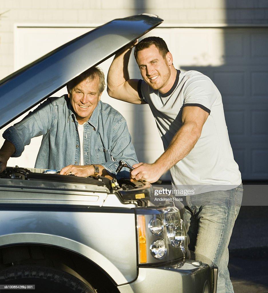 Portrait of two men examining engine of car : Foto stock