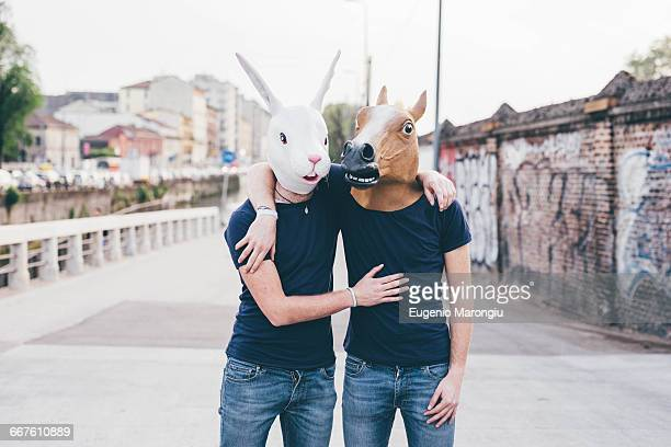 Portrait of two men wearing rabbit and horse masks on urban bridge