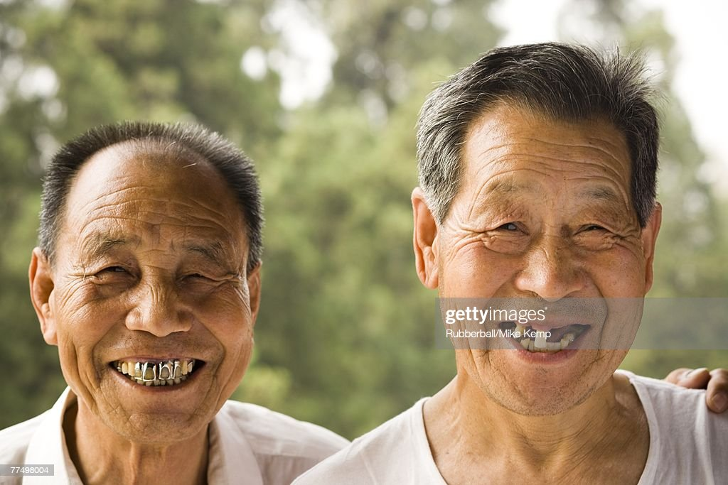 Portrait of two men with bad teeth smiling outdoors : Stock Photo