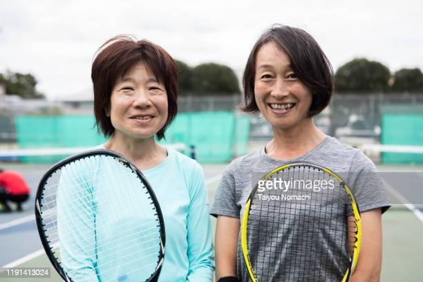 portrait of two middle-aged women enjoying tennis - スポーツ  ストックフォトと画像