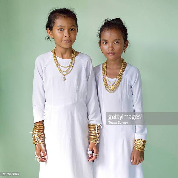 Portrait of two Muslim Cham girls wearing white dresses and bronze and copper jewellery at their Karoh ceremony in Van Lam Ninh Thuan province...