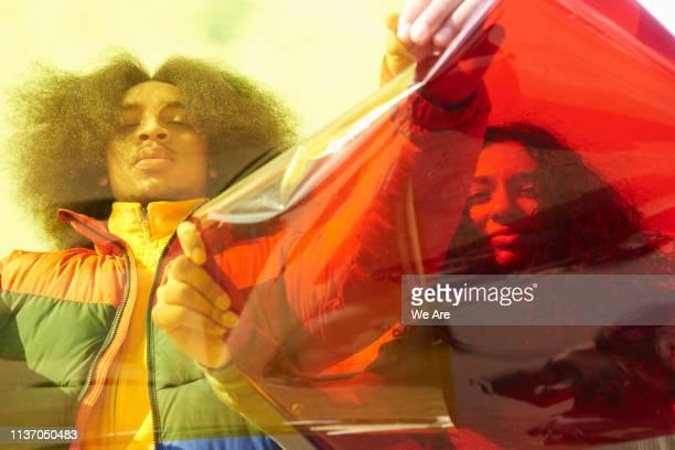 portrait of two people behind cellophane - farbquadrat stock-fotos und bilder
