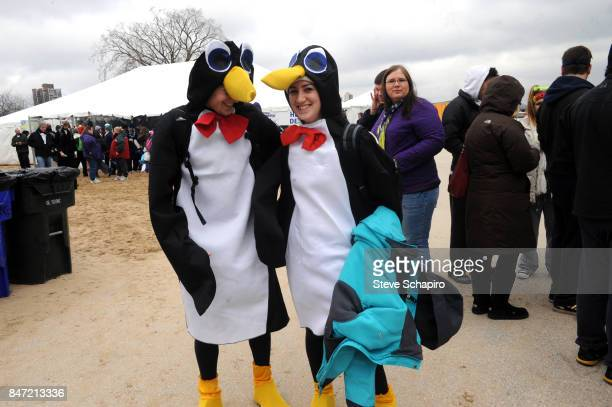 Portrait of two people in matching penguin costumes as they pose on North Avenue Beach during a Chicago Polar Plunge event Chicago Illinois 2010