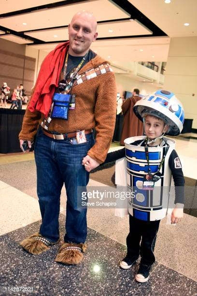 Portrait of two people, one adult dressed as a 'Wookie' and a child dressed as 'R2D2,' at the Star Wars Celebration event at Wintrust Arena, Chicago,...