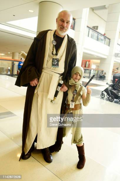 Portrait of two people, one adult dressed as 'Obi-Wan Kenobi' and a child dressed as 'Rey,' at the Star Wars Celebration event at Wintrust Arena,...