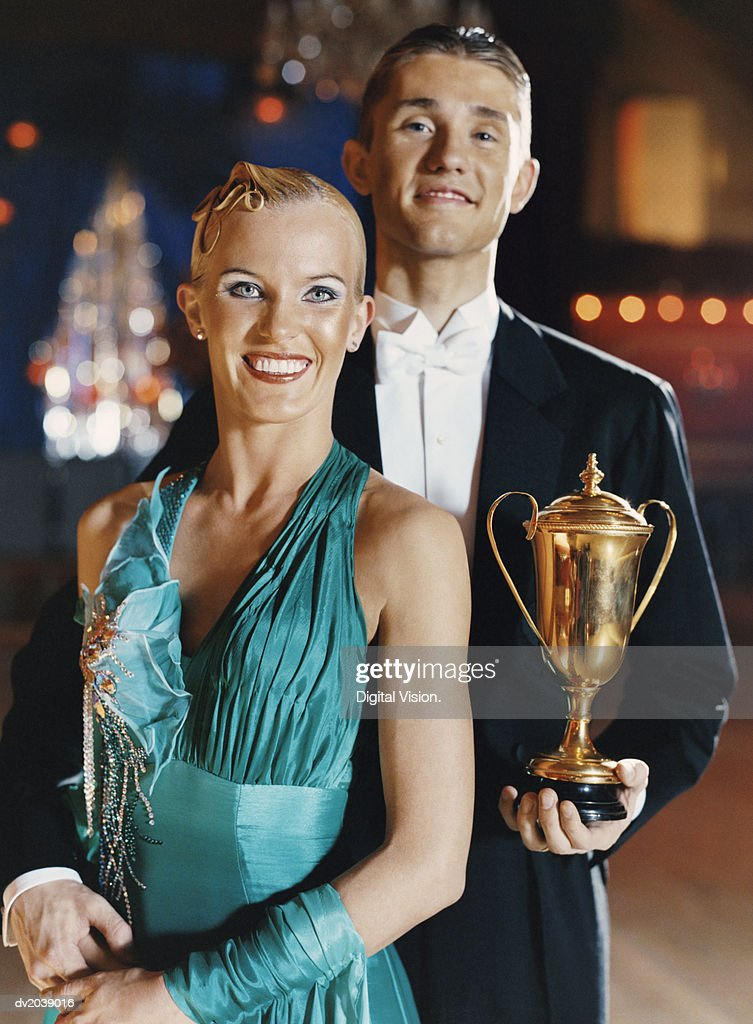 Portrait of Two Proud Ballroom Dancers Standing Together on a Dance Floor, with the Man Holding a Trophy : Stock Photo