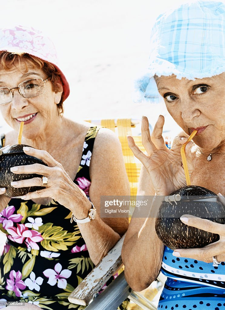 Portrait of Two Senior Women in Swimming Costumes and Sunhats Drinking Coconut Cocktails : Stock Photo