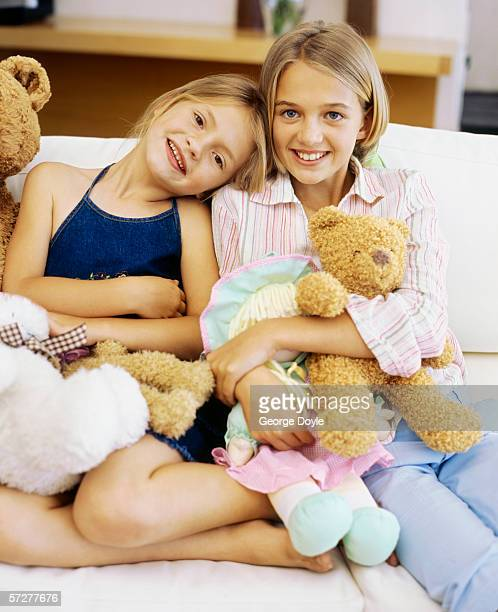 portrait of two sisters holding toys and smiling - only girls stock pictures, royalty-free photos & images