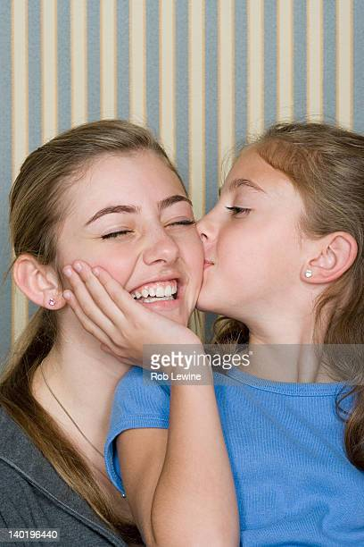 Portrait of two sisters (14-15, 8-9) kissing