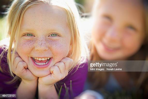 A portrait of two sisters smiling. Two young girls, with blue eyes and blonde hair. Lying on the grass. Close up.