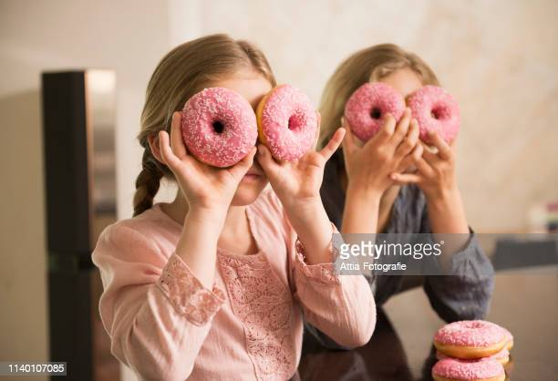portrait of two sisters with doughnut holes over their eyes - nur kinder stock-fotos und bilder