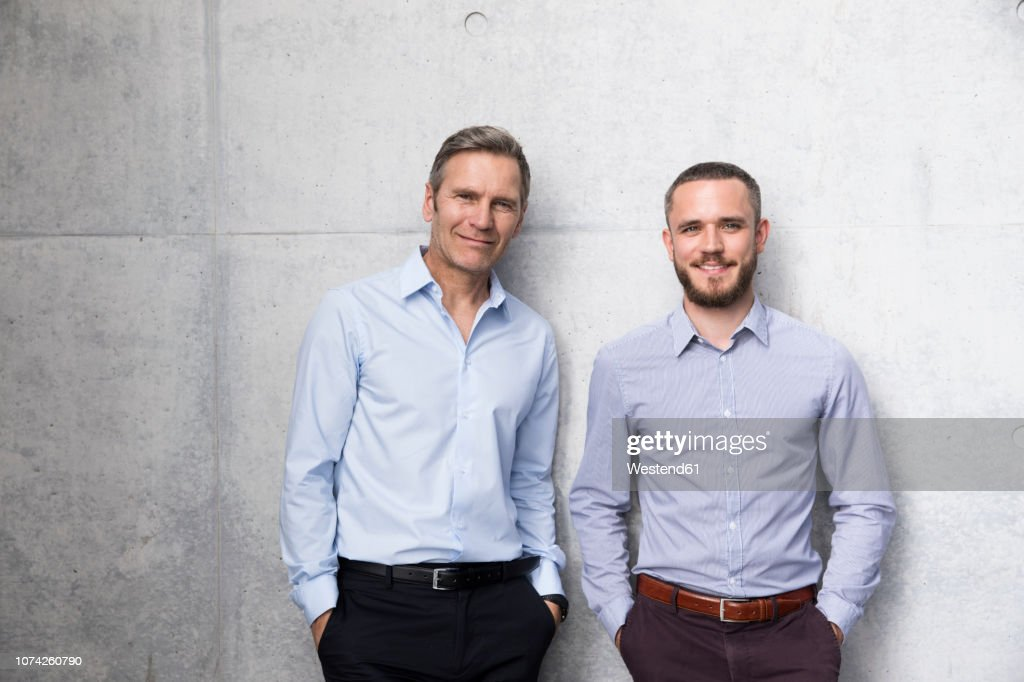 Portrait of two smiling businessmen at a wall : Stock-Foto