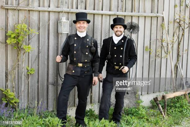 portrait of two smiling chimney sweeps standing at wooden wall - schornsteinfeger stock-fotos und bilder