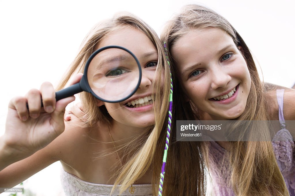 Portrait of two smiling girls with magnifying glass : Stock Photo