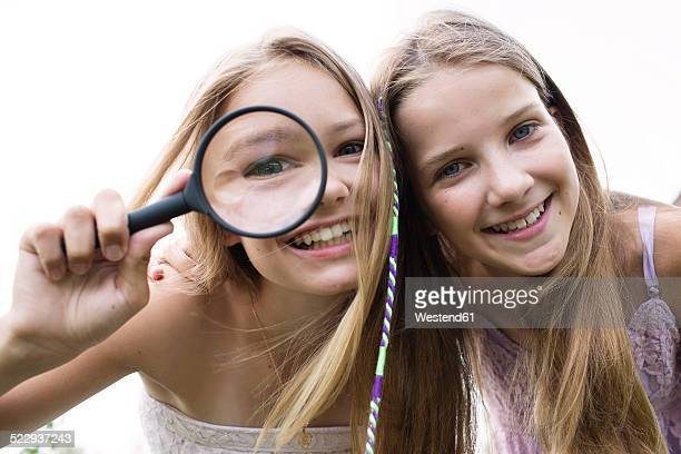 portrait of two smiling girls with magnifying glass - little girls bent over stock photos and pictures