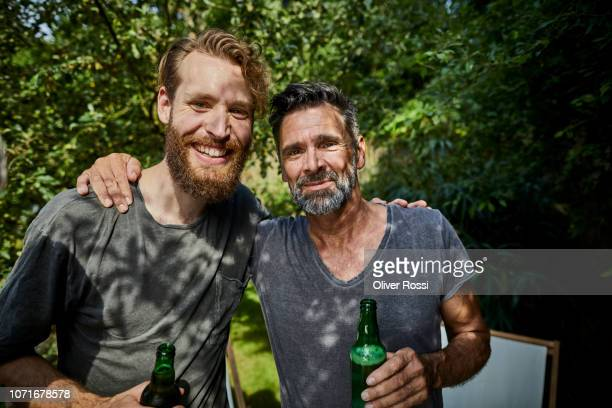 portrait of two smiling man with beer bottles embracing in garden - men friends beer outside stock pictures, royalty-free photos & images