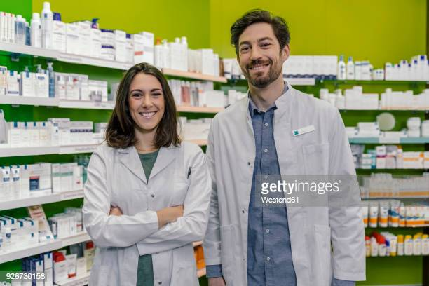 portrait of two smiling pharmacist at shelf with medicine in pharmacy - 机上のネームプレート ストックフォトと画像