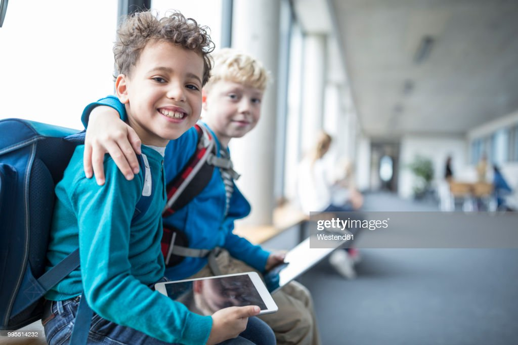 Portrait of two smiling schoolgboys with tablet embracing : Stock Photo