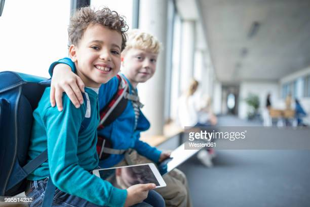 portrait of two smiling schoolgboys with tablet embracing - schulgebäude stock-fotos und bilder