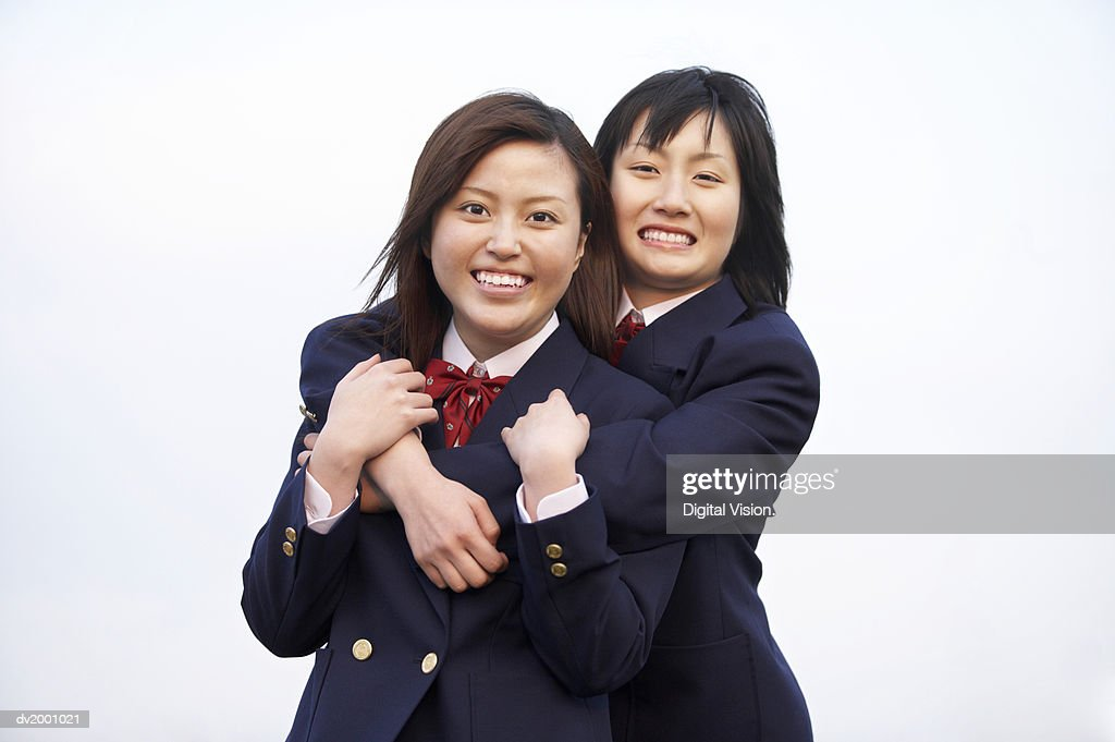 Portrait of Two Smiling Schoolgirls With Their Arms Around Each Other : Stock Photo