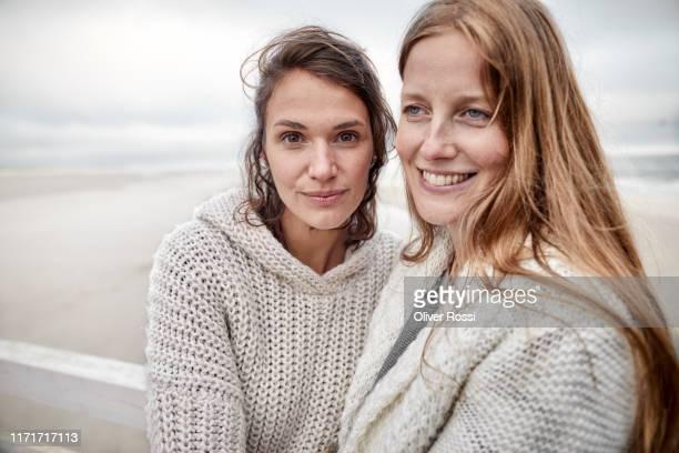 portrait of two smiling women by the sea - weibliche freundschaft stock-fotos und bilder