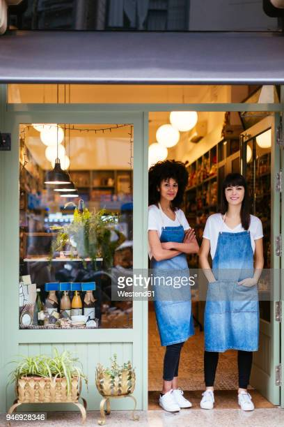 Portrait of two smiling women standing in entrance door of a store