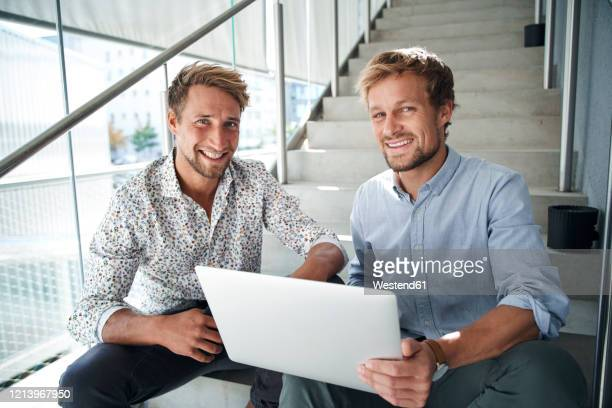 portrait of two smiling young businessmen sitting on stairs with laptop - oprichter stockfoto's en -beelden