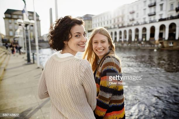 portrait of two smiling young women by the riverside - freundin stock-fotos und bilder