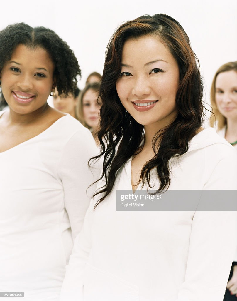 Portrait of Two Smiling Young Women in White Long-Sleeved Tops Standing in a Crowd : Stock Photo