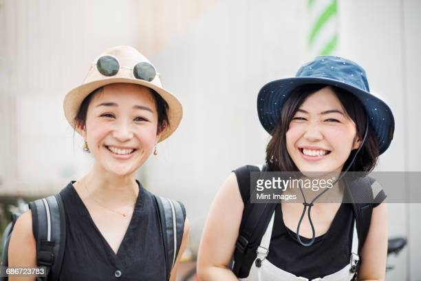 Portrait of two smiling young women wearing hats.