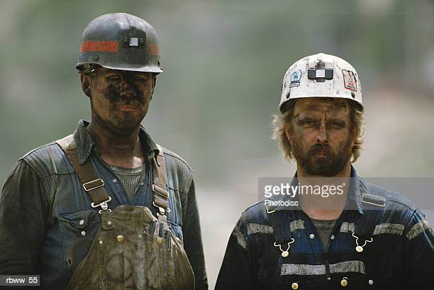 portrait of two soiled hard-working caucasian coal miners