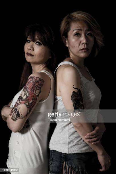 Portrait of two tattooed Japanese women taken with a dramatic black background