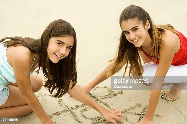 Portrait of two teenage girls drawing on sand on the beach