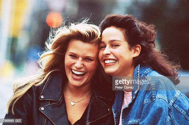 Portrait of two teenage girls laughing outdoors