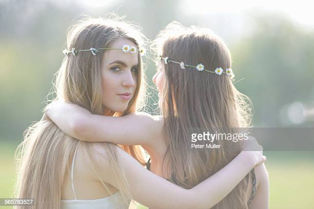 Portrait of two teenage girls wearing daisy chain headdresses in park