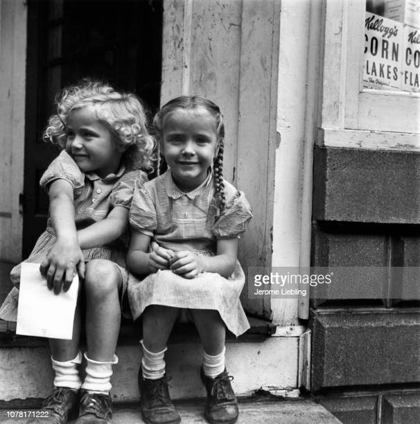 Portrait of two unidentified blonde girls both in gingham dresses as sit in the doorway of a shop and smile Hinsdale Massachusetts 1949 Visible in...