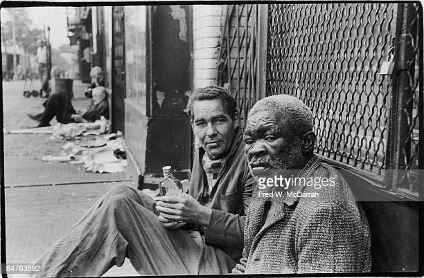 Portrait of two unidentified homeless men as they sit on a sidewalk on the Bowery New York New York June 30 1969