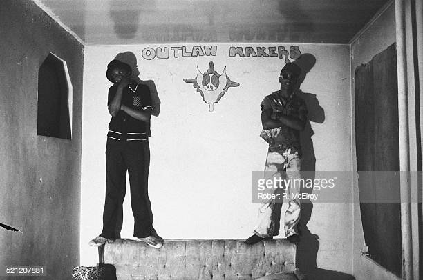 Portrait of two unidentified members of Bronx street gang the Outlaw Makers as they stand on a couch in their clubhouse New York New York 1975